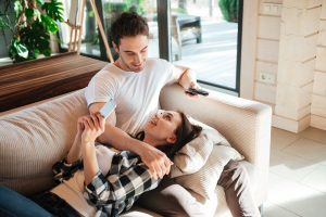 Talking smiling woman lying on couch with her man holding remote controoler in living room